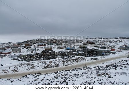 View of Cape Dorset, Nunavut with a layer of snow on the ground with the high school recently burned down, Canada stock photo