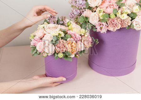 perfect gift or compliment. bouquet in green hatbox. beautiful luxury bunch of mixed flowers in womans hand. the work of the florist at a flower shop stock photo