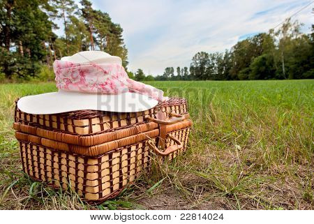 picnic basket with straw hat, on green grass stock photo