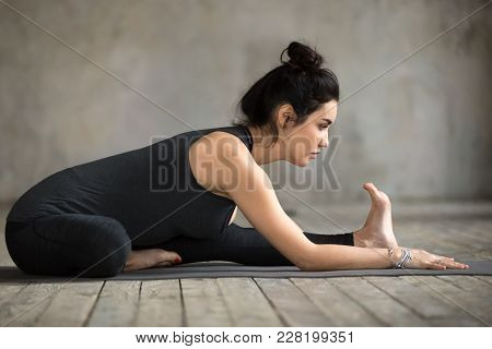 Young woman practicing yoga, doing Head to Knee Forward Bend exercise, Janu Sirsasana pose, working out, wearing sportswear, black pants and top, indoor full length, gray wall in yoga studio stock photo