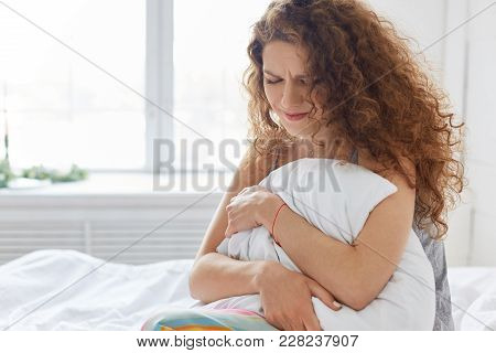 Crying young female with curly hair, feels desperately after quarrel with husband, sits on bed in bedroom, feels lonely and exasperate. Woman suffers from pain, stays in bed all day alone stock photo