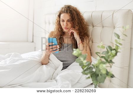 Adorable young woman in pyjama, holds modern smart phone, reads email form friend attentively on mobile application, connected to wireless internet in bedroom, spends leisure time in bedroom stock photo