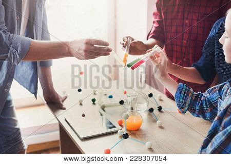 Pupils with teacher doing biochemistry research in chemistry class, using laboratory tubes with colorful liquids. Stem education. Early development, education, diy, innovation concept. stock photo