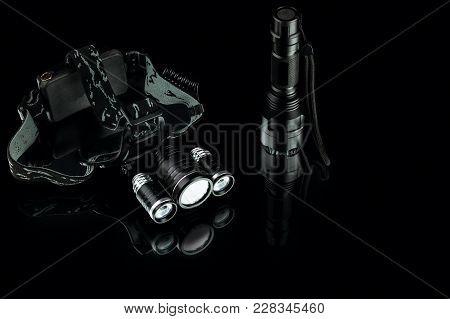 anodized aluminium waterproof tactical flashlight and headlamp on black background stock photo