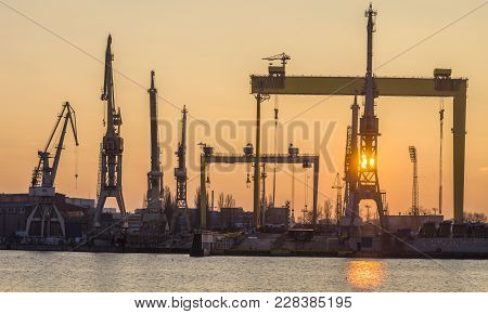 Silhouettes of cranes and gantry cranes in the light of the setting sun. Shipyard in Szczecin stock photo