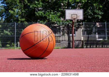 Outdoors basketball court with basketball ball during sunny day stock photo