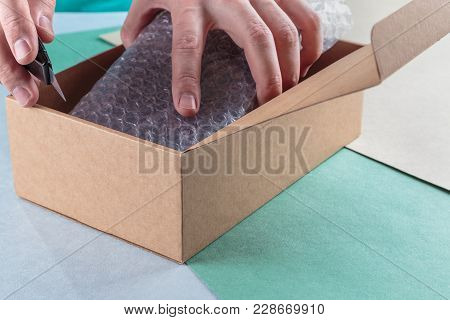 unboxing the parcels Packed in a cardboard box with a utility knife stock photo