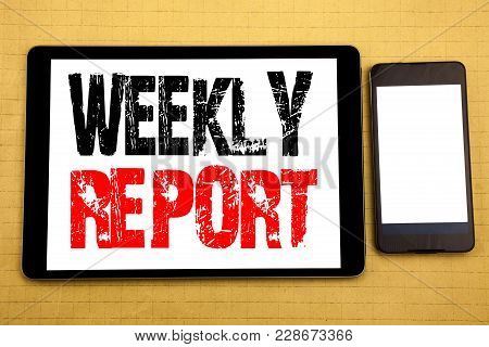 Hand writing text caption inspiration showing Weekly Report. Business concept for Analyzing Performance  Written on tablet, wooden background with sticky note and pen stock photo
