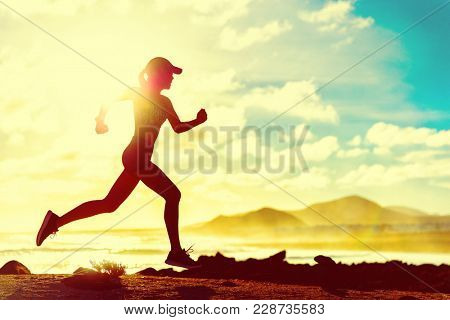 Summer fitness healthy active woman running on beach against sun flare at sunset. Runner athlete spo