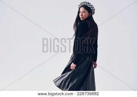 Gorgeous portrait of elegant asian woman in fashionable black skirt and beret isolated on white background stock photo