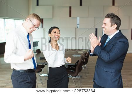 Happy mid adult Caucasian leader congratulating his team, man and Asian woman, with success and applauding. Young people showing winning gesture. Cooperation and success concept stock photo