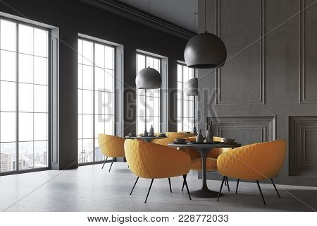 Black restaurant corner with a concrete floor, round black tables and yellow chairs. A blank wall fragment. 3d rendering mock up stock photo