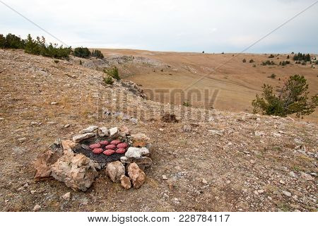 Campfire firepiit with food on it at sunrise in the Pryor mountains in Montana United States stock photo
