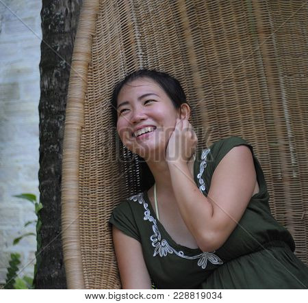 portrait of young sweet and relaxed Asian Chinese woman on her 20s wearing green Summer dress smiling happy and playful sitting at bamboo swing chair in holidays and vacation travel concept stock photo