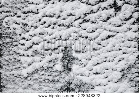 Snow on a dark surface after a snowfall. The texture of the snow. stock photo