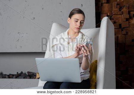 Woman content writer for business presentation using mobile phone during work on laptop computer. Female intelligent entrepreneur booking on-line via cellphone after video conference on net-book stock photo