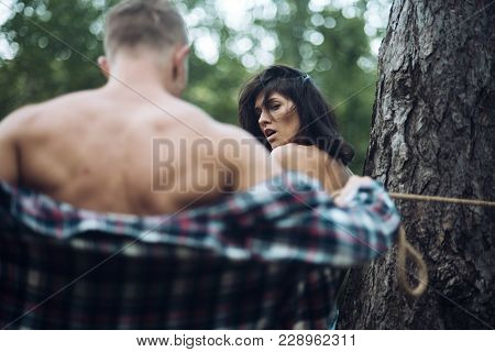 Kidnapper or robber tied young girl with rope to tree, force to have sex. Dominate man kidnapped nude girl at forest, defocused. Sexual abuse concept. Female victim of rape, violence and criminal. stock photo