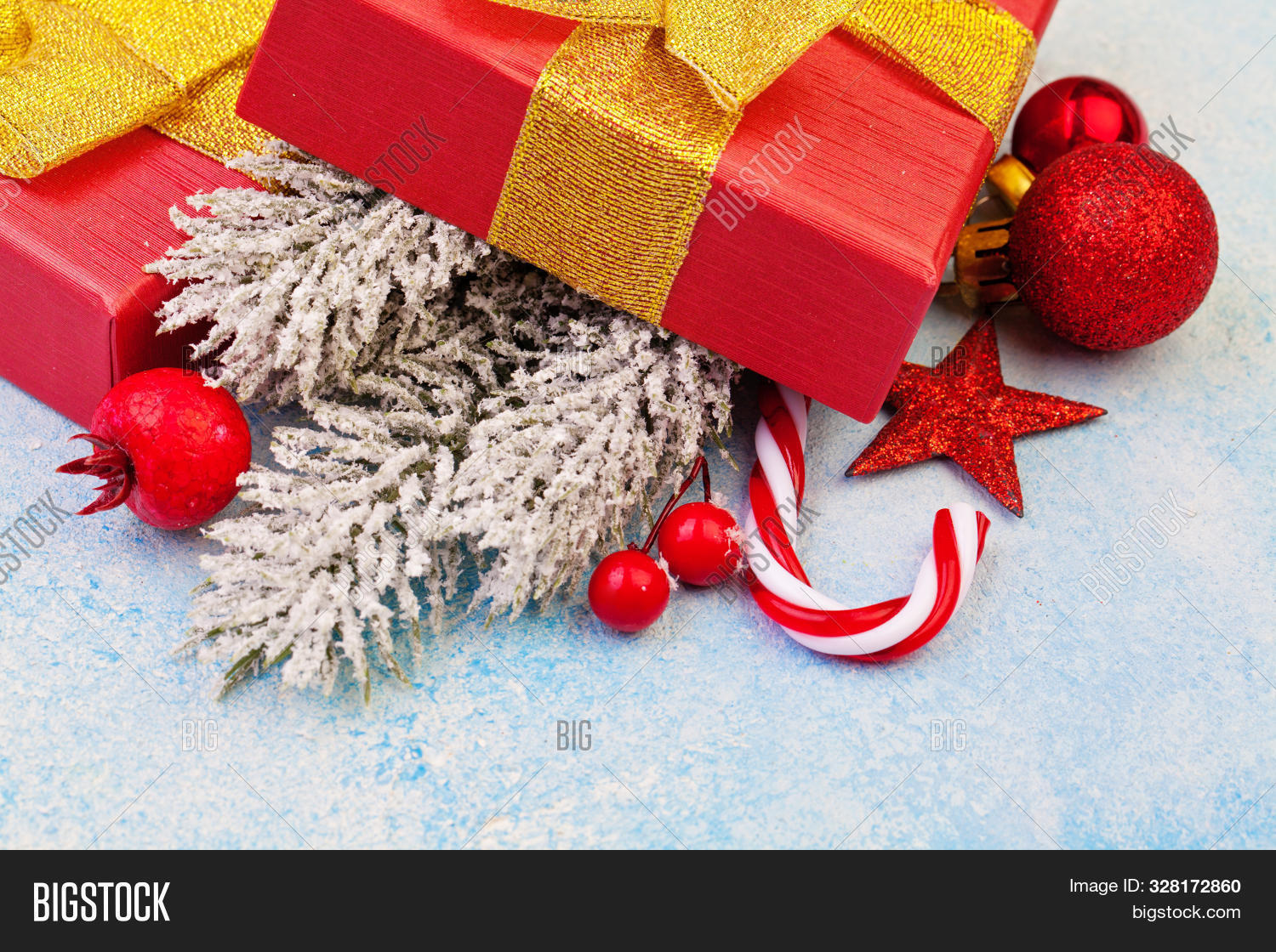 Christmas Concept. Red Gift Box,  Xmas Decorations And Green Winter Frozen Fir Branches On Blue Froz