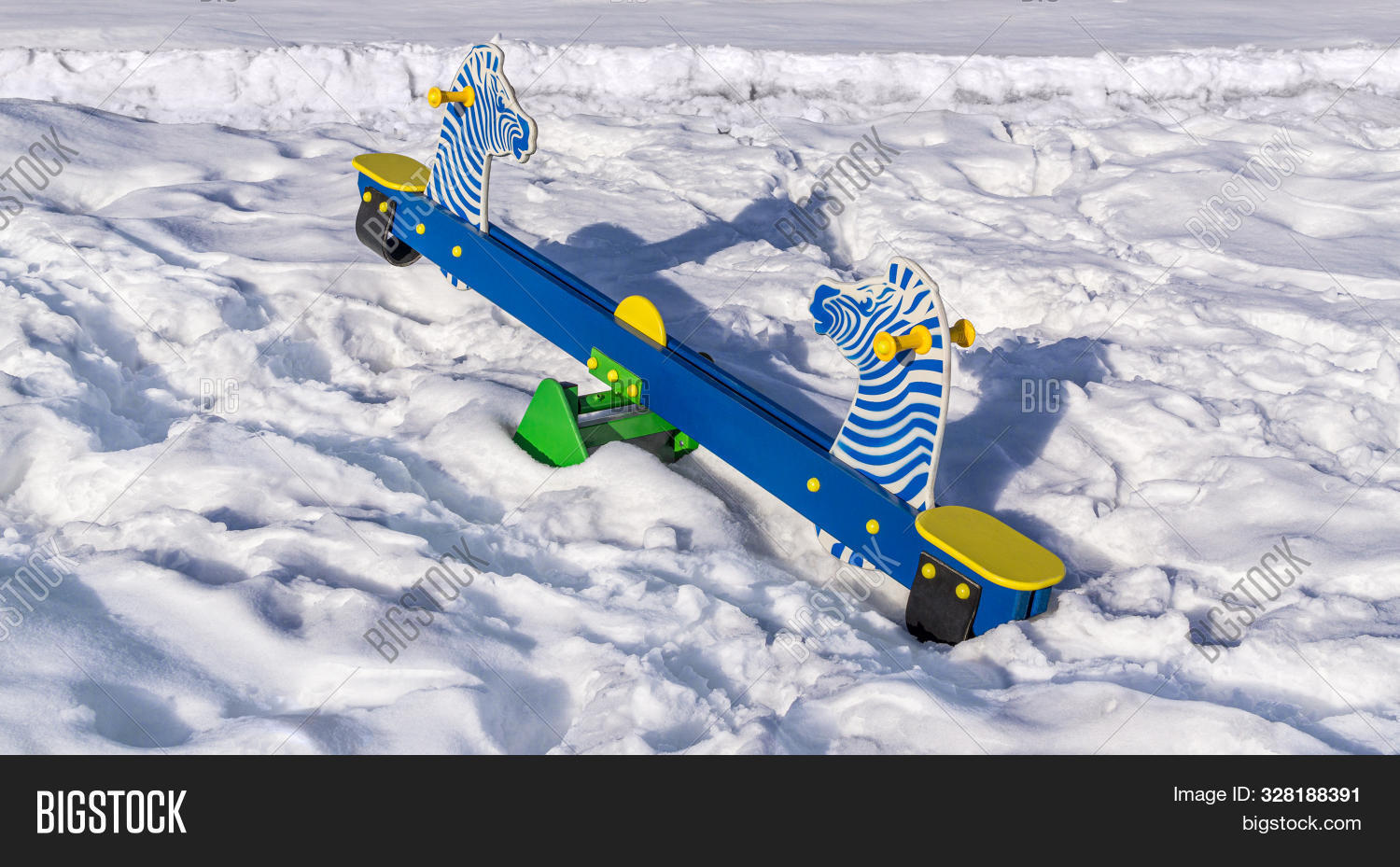 Seesaw In Shape Of Zebras Is On Snowy Playground. Winter Sunny Day. Copy Space