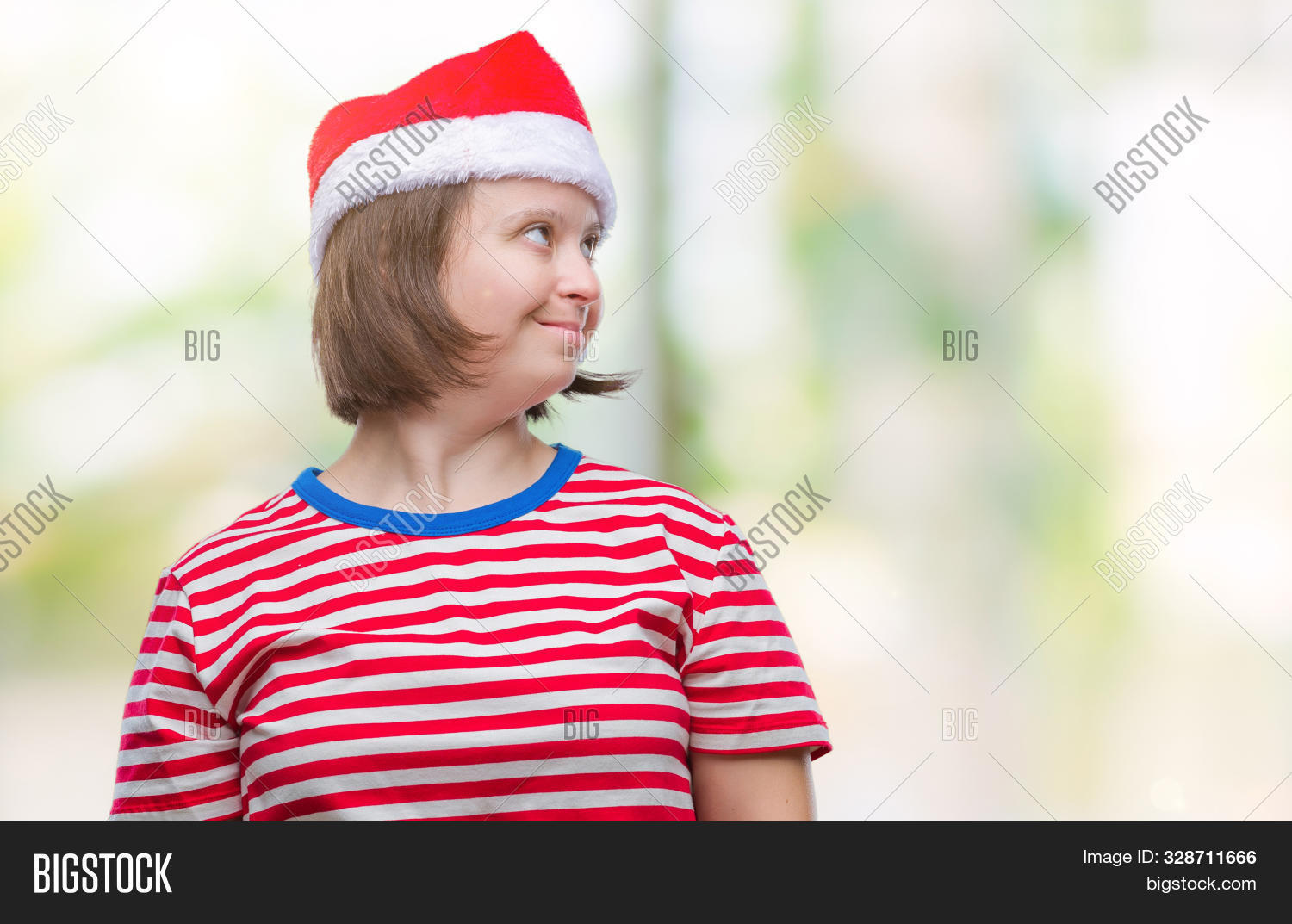 Young adult woman with down syndrome wearing christmas hat over isolated background looking away to