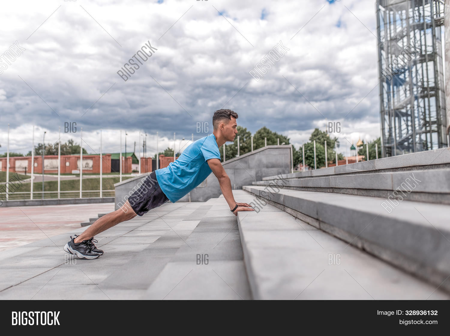 male athlete pushing up steps, in summer day in city, background cloud. Active youth lifestyle, fitness workout in nature. Free space for text strength and motivation. Strong man.