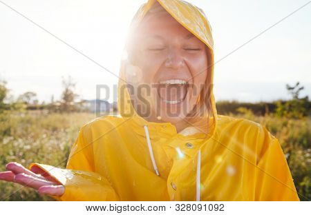 Unhappy Woman Wearing Waterproof Coat At Outdoor Music Festival stock photo