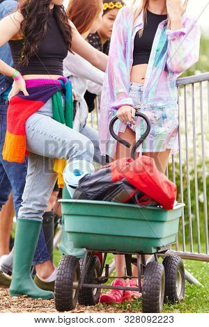 Friends Pulling Trolley As They Arrive At Music Festival Carrying Camping Equipment Onto Site stock photo