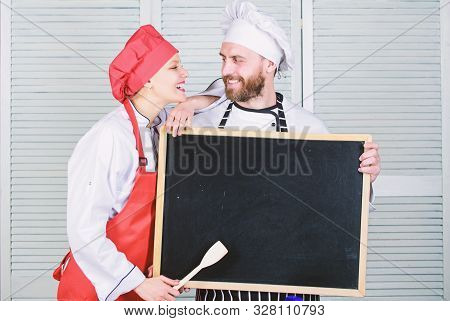 Private cooking school. Master cook and prep cook giving cooking class. Chef and cook helper teaching master class. Couple of man and woman holding empty blackboard in cooking school, copy space stock photo
