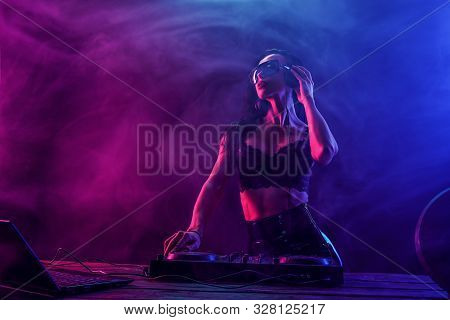 Young sexy woman dj in bra and sunglasses playing music. Headphones and dj mixer on table. Colorful Smoke on background stock photo