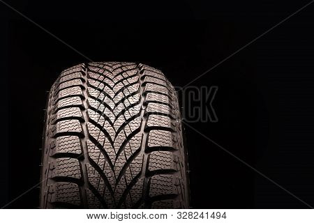 new directional friction winter tire Velcro without spikes on black background. rubber for ice water and snow. seasonal change of tyres in the autumn or winter. free space for text and information. stock photo
