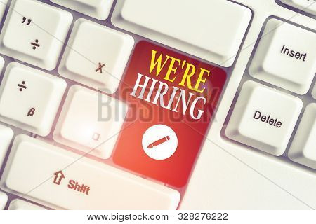 Handwriting text writing We Re Hiring. Concept meaning Advertising Employment Workforce Placement New Job White pc keyboard with empty note paper above white background key copy space. stock photo