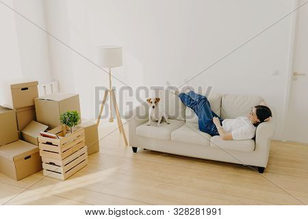 Female renter lies on white comfortable couch, raises crossed legs, poses with favourite dog, has new dwelling in living room, enjoys relocation day, feels relaxed. New home and relocation concept stock photo