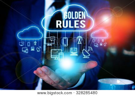 Writing note showing Golden Rules. Business photo showcasing Basic principle that should be followed Important Principle Male wear formal work suit presenting presentation smart device. stock photo
