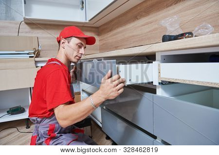 kitchen installation. Worker assembling furniture stock photo