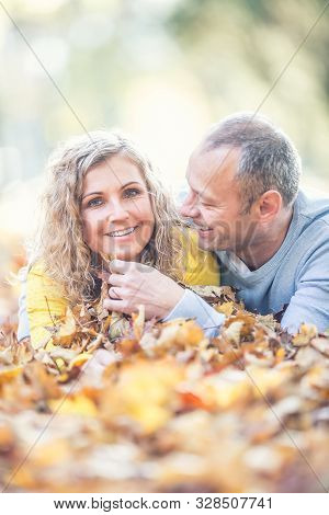 Happy senior couple lying in autumn maple leaves. stock photo