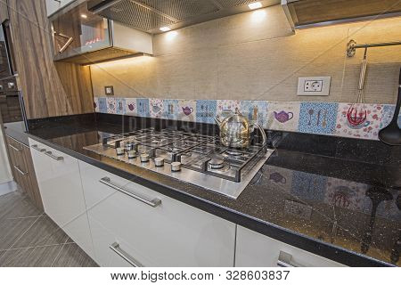 Interior design decor showing modern kitchen cooker hob appliance with extractor fan in luxury apartment showroom stock photo