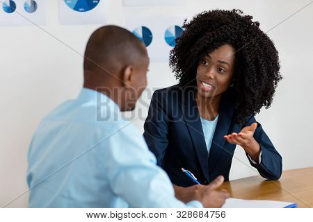African american businesswoman talking with customer about contract at office stock photo