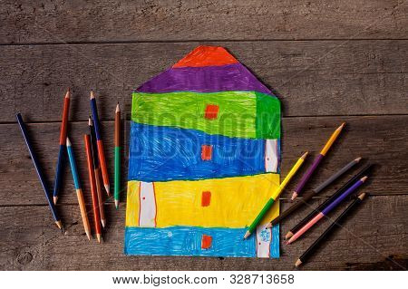 Child drawing of a house on a wooden background stock photo