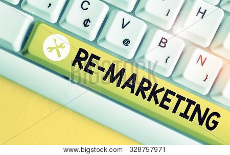 Conceptual hand writing showing Re Marketing. Business photo text Strategy to reach potential customers in your website White pc keyboard with note paper above the white background. stock photo