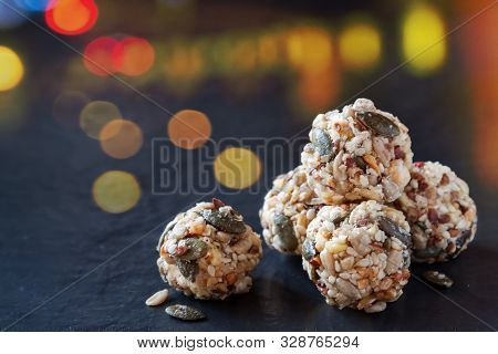 Handmade no bake organic seeds nuts vegan almond energy balls on black slate of tile with yellow red bokeh lights background stock photo