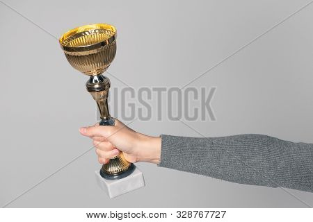 Golden award cup in winner hand isolated on gray background. Award ceremony. stock photo