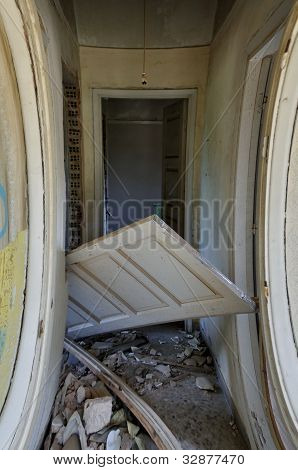Unhinged door and debris in the corridor of an abandoned house. stock photo