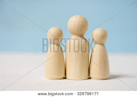Close up of wooden figures of man with two woman or adult with two children. stock photo