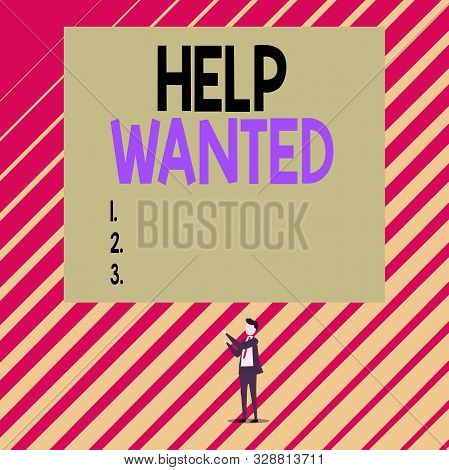 Text sign showing Help Wanted. Conceptual photo An ad in the paper an employer places to find a new employee Short hair immature young man stand in front of rectangle big blank board. stock photo