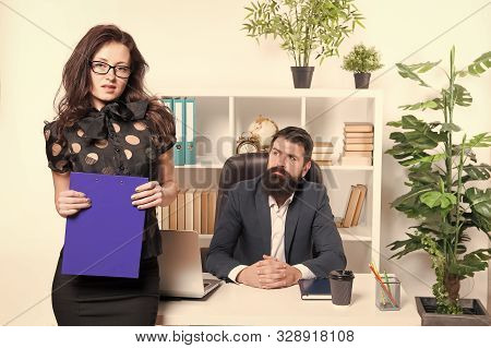 Sensual but professional. Sensual business lady. Sensual woman standing in front of businessmen in office. Adorable girl with sensual look holding folder. Sexy secretary and her boss. stock photo