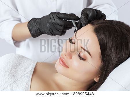 The doctor cosmetologist makes the Rejuvenating injections procedure for tightening and smoothing wrinkles on the face skin of a beautiful woman in a beauty salon.Cosmetology skin care. stock photo