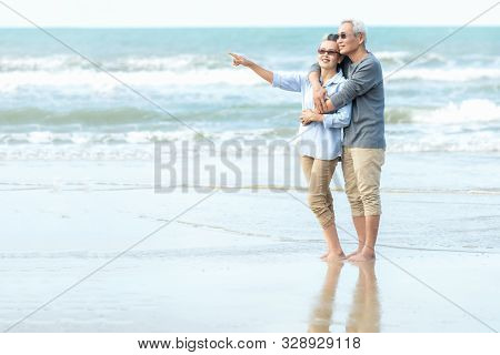 Asian Lifestyle senior couple hug on the beach happy in love romantic and relax time. Tourism elderly family travel leisure and activity after retirement in vacations and summer. stock photo