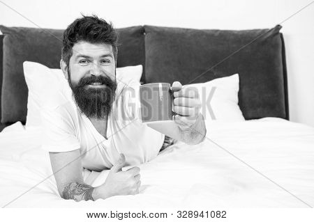 Full of energy. Coffee affects body. Man handsome hipster relaxing on bed with coffee cup. Bearded hipster enjoy morning coffee. Morning becomes much better with good coffee. Relax and rest. stock photo