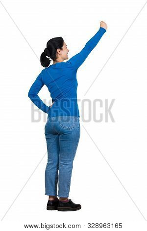 Rear view of cheerful brunette woman full length portrait raising arm as holding something imaginary, looking up confident. Brave girl gesture hold an invisible object isolated on white background. stock photo
