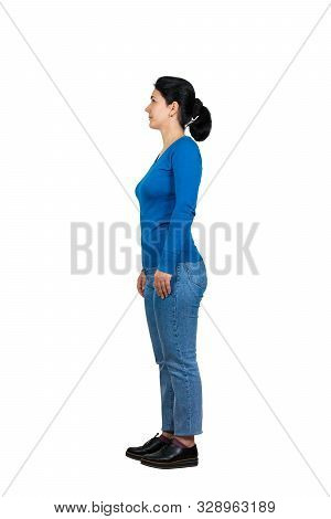 Full length side view of casual young woman standing relaxed looking ahead isolated over white background. stock photo